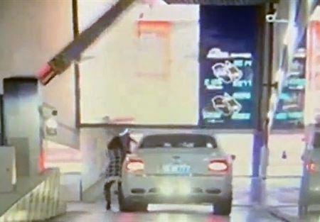 """بالفيديو.. امرأة تحطم """"بنتلي"""" فاخرة في موقف للسيارات"""