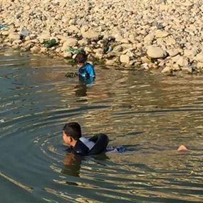 بالصور: طفلان يسبحان في مستنقع مياه ملوثة