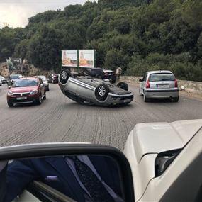بالصورة: انقلاب سيارة على طريق عام بلونة