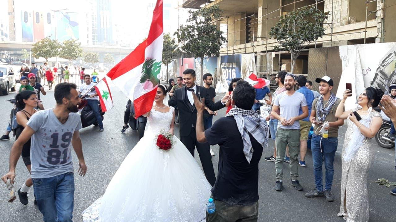 نتيجة بحث الصور عن عروسين يحتفلان بزفافها وسط المتظاهرين بلبنان